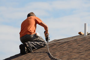 Replacing shingles on a wind damaged roof that was allowing water to leak in
